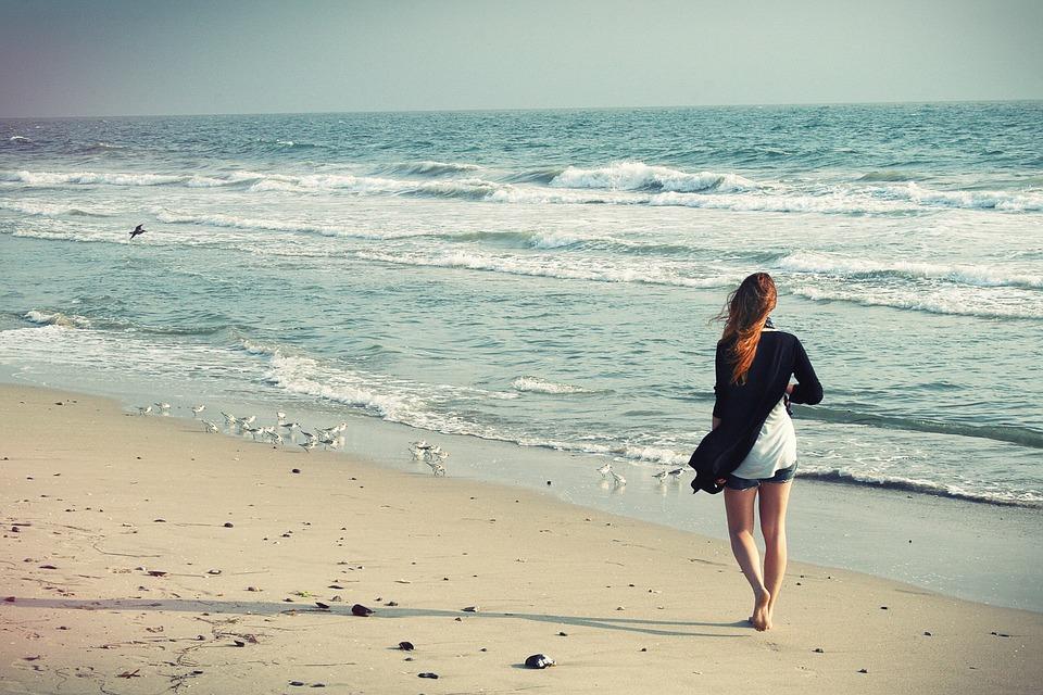 Frau am Strand mit enthaarten Beinen